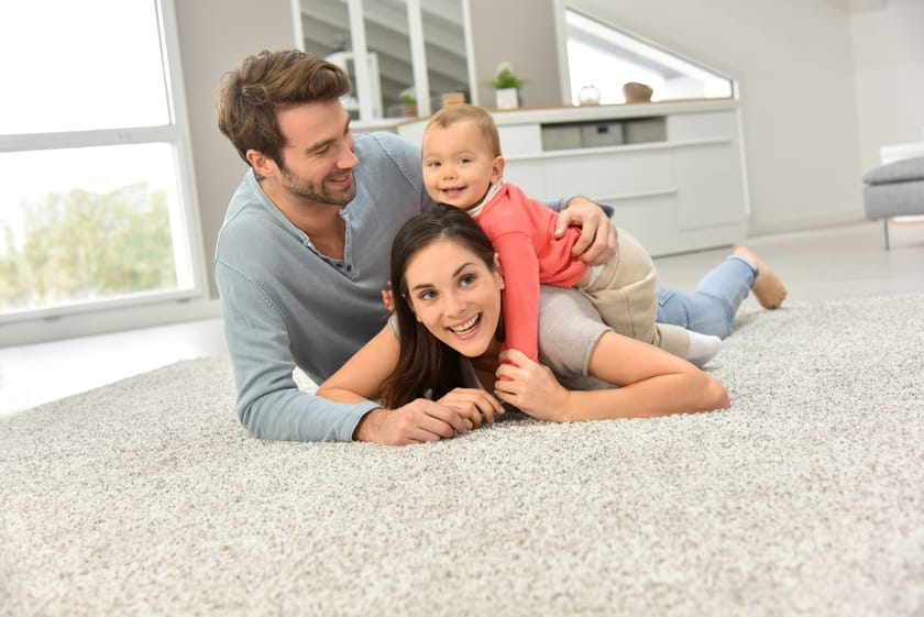 mother father and baby all playing on clean rug